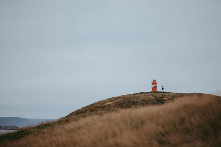 Low angle view of lighthouse on hill against sky