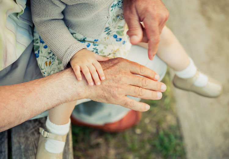 Baby girl touching hand of senior man. Two different generations concept. Horizontal Family Outdoors Nature Togheter Love Summer Generations Hand Unrecognizable People Grandparent Granddaughter Baby Girl Sitting Senior Adult Mature Elderly Skin Security Aged SUPPORT Two People Holding Touching