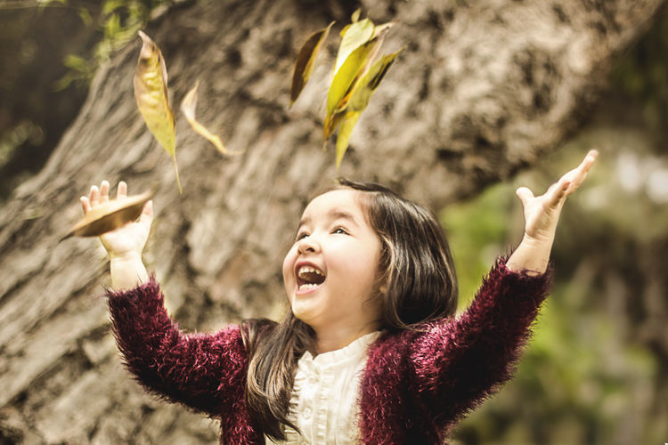 Close-up of cheerful girl throwing leaves
