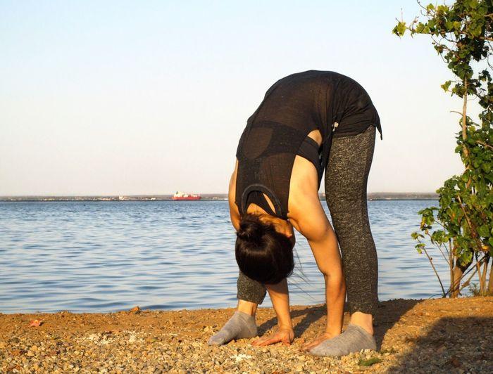 Full Length Of Woman Exercising On Beach Against Clear Sky