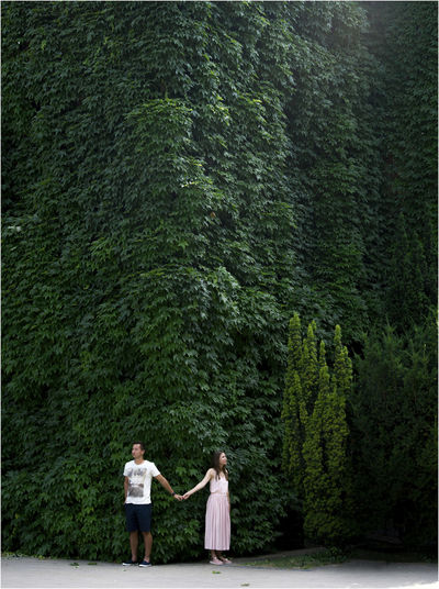 Couple Holding Hands While Standing Against Ivy