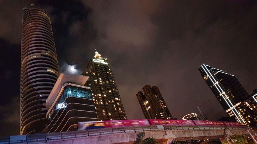 Low angle view of skyscrapers lit up at night