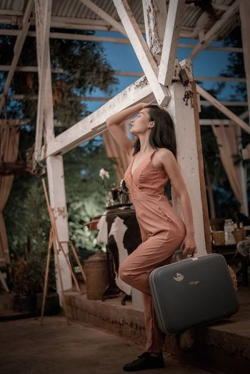 Side view of female model holding suitcase while standing in built structure