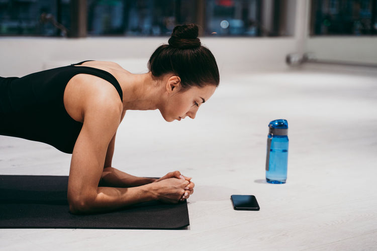 Side view of woman planking at gym