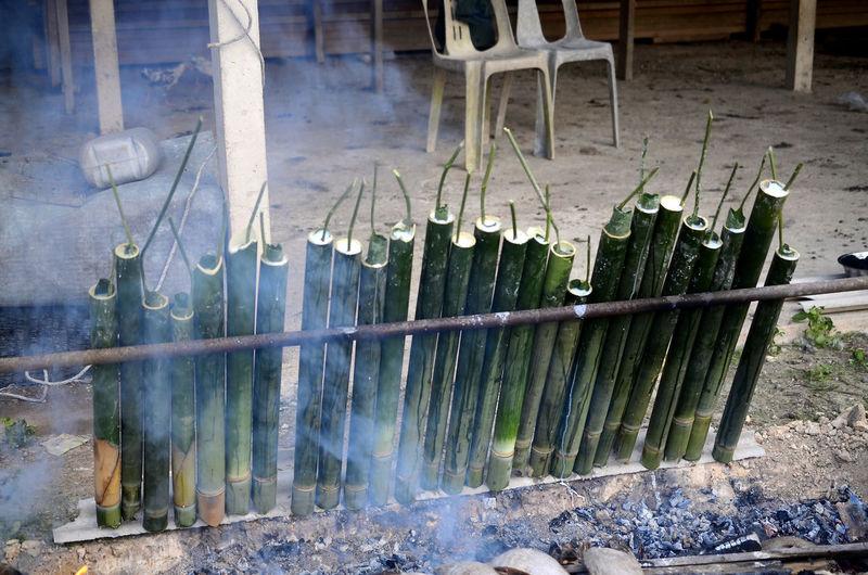 lemang or bamboo glutinous rice dumpling for hari raya festive in asian in slow cooking method Hot Food Hari Raya Aidilfitri Coconut Leaf Bamboo Rice Coconut Burned Slow Cooking Ash Smoke Flame Shapes Prepared Food Served
