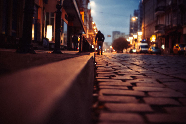 Surface level view of cobbled street amidst buildings at night