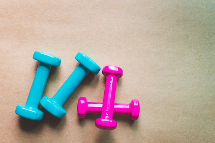 Fitness Equipment Dumbbell Gym Still Life Indoors  Close-up No People Multi Colored Pink Color Weight High Angle View Weights Plastic Exercise Equipment Weight Training  Studio Shot Group Of Objects Sports Training Table Blue