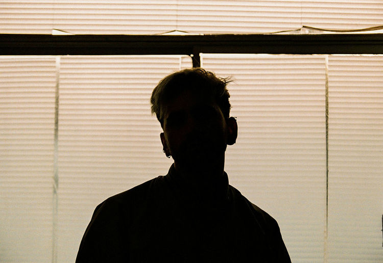 Portrait of silhouette man standing against window