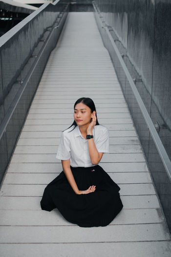 High angle view of woman looking away while sitting on walkway
