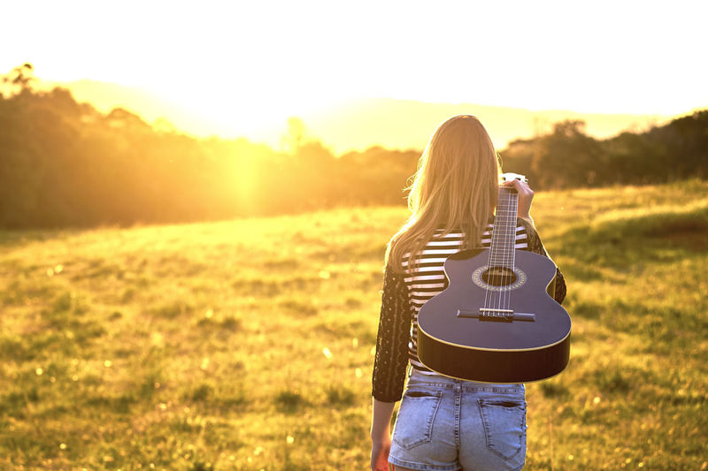 Rear View Of Woman Carrying Guitar On Field