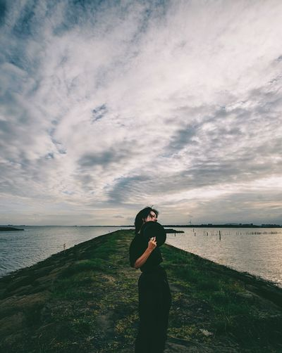 Man photographing on sea against sky