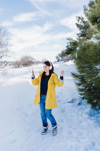 Full length portrait of woman standing on snow covered tree