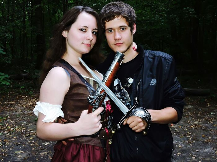 Portrait Of Young Couple Holding Weapons In Forest