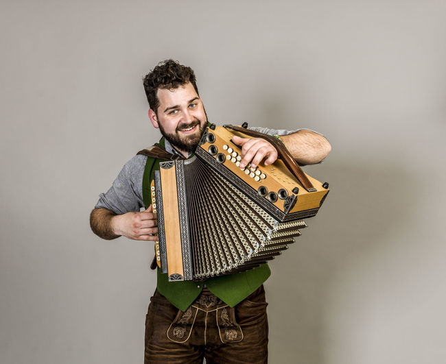 Musician Costume Leather Trousers Tradition Traditional Austria Green Pose Accordion Man Young Shorts Friendly Proud Happy Play Music Fun Joy Single One Background Copy Space Studio Entertainment Mountains Shirt STAND Hobby Leisure Cool Studio Shot Indoors  One Person Smiling Young Adult Three Quarter Length Standing Front View Musical Instrument Portrait White Background Arts Culture And Entertainment Gray Background Young Men Playing Men Holding Gray
