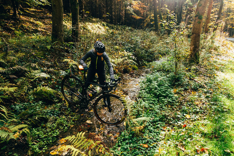 Woman holding bicycle in forest