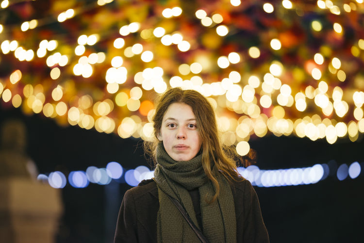 Portrait of woman standing against illuminated lights during winter