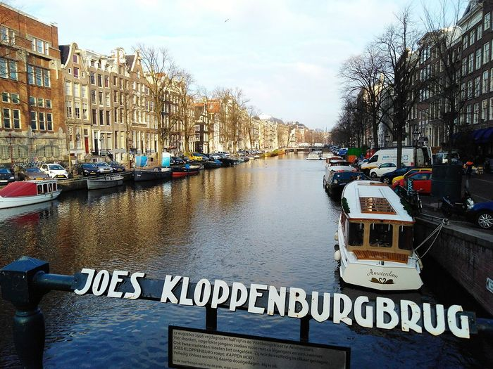 a view of Amsterdam's Joes Kloppenburgbrug bridge with a sign in the foreground with its name Bridge Joes Kloppenburgbrug Dutch Water Nautical Vessel Tree Communication Text Western Script Sky Architecture Moored Information Boat Canal Signboard