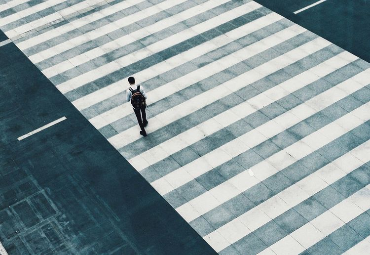 High angle view of man walking on zebra crossing in city