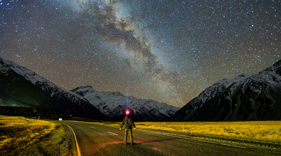 Man standing on road under Milky Way with snow capped Southern Alps in the background. Mount Cook National Park, New Zealand Adult Adventure Astronomy Beauty In Nature Galaxy Glacier Landscape Milky Way Mountain Mountain Range Nature Night One Man Only One Person Outdoors People Science Sky Space Space And Astronomy Space Exploration Star - Space Summer Young Adult