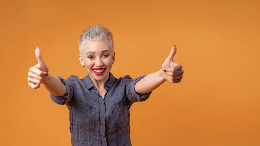 Portrait of happy woman showing thumbs ups against orange background