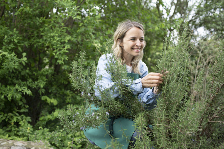 Young woman smiling while holding plants against trees