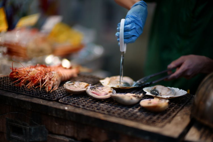 Midsection of person preparing meat on barbecue grill