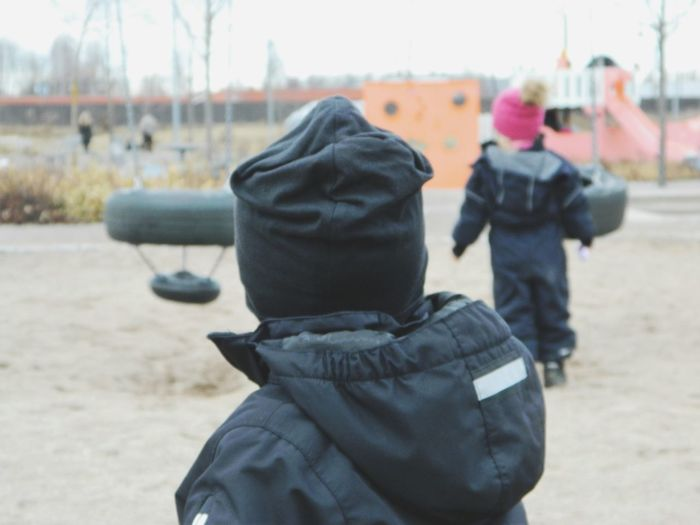 Children wearing warm clothing playing in playground
