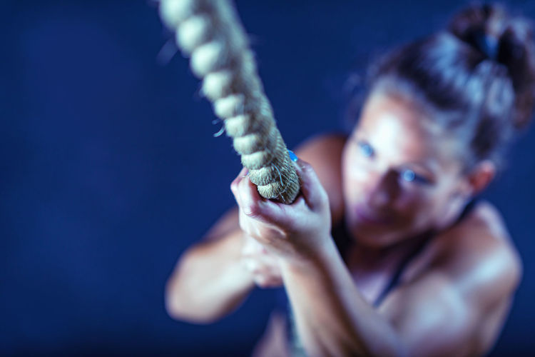 High angle view of female athlete climbing on rope in gym