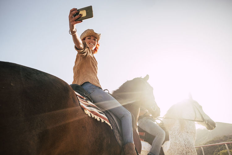couple riding horses take a selfie with modern technology smartphone. cowboy lifestyle and smile woman. sunset time and backlight for outdoor leisure activity for friends Cowboy Arms Raised Domestic Animals Horse Human Arm Leisure Activity Lens Flare Lifestyles Livestock Mammal Nature One Person Outdoors Pets Real People Riding Selfie Sitting Sky Smart Phone Sunlight Technology Two People Women Young Couple