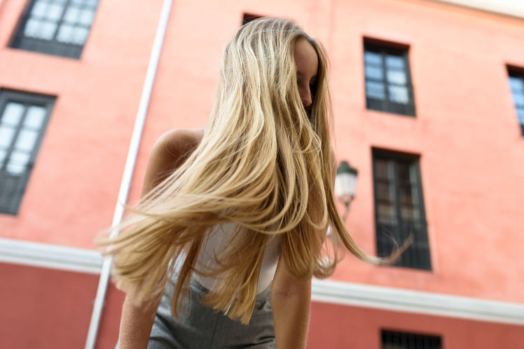 Low angle view of woman tossing blond hair against building