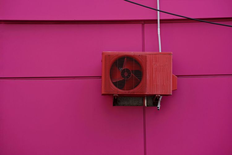 Air conditioner compressor on pink wall