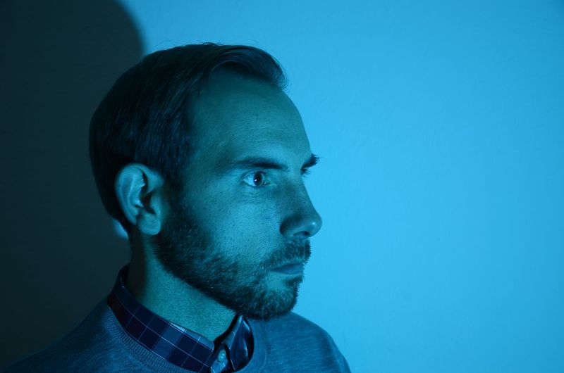 Bearded Man In Profile Cold Blue Light Man With Intense Look Winter Fashion Blue Headshot One Man Only Receding Hairline Studio Shot