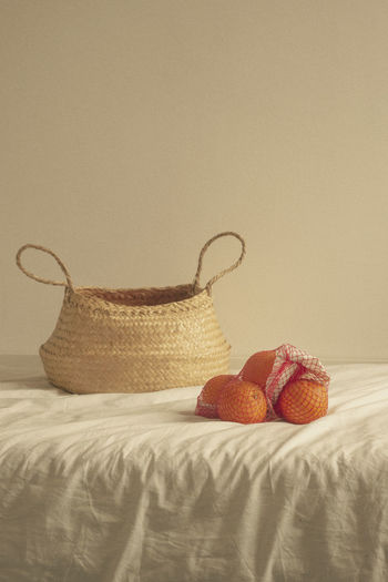 Wicker basket on bed against wall at home