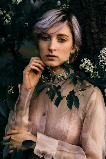 Fashion Beautiful Woman Delicate Dyed Hair Flower Flowering Plant Front View Hairstyle Lifestyles Looking At Camera Nature One Person Outdoors Portrait Purple Hair Real People Young Adult