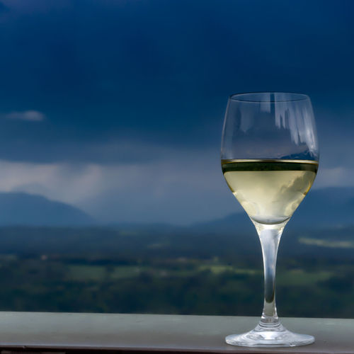 Selective focus on a drink of white wine on a counter overseing mountains in the background and approaching rain, with plenty of copy space viewed from the side Selective Focus Glass White Wine Cup Counter Mountains Background Approaching Rain Blue Green Sky Copy Space Copy-space Nobody Alcoholic  Drink Beverage Toast Country Countryside Bucolic One Glass No Person High Side View Celebrating Celebration Drinking Wine Country Refreshment Transparent Food And Drink Alcohol Wineglass Glass - Material Focus On Foreground No People Still Life Table Close-up Day Freshness Drinking Glass Nature Single Object Household Equipment Purity