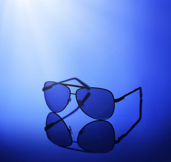 Sunglasses in blue light on a reflective background. Blue Studio Shot No People Glasses Blue Background Still Life Transparent Single Object Reflection Personal Accessory Sunglasses Eyewear