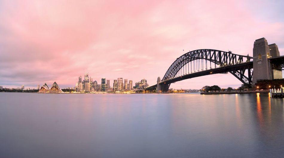 Sydney harbor bridge over parramatta river in city during sunset