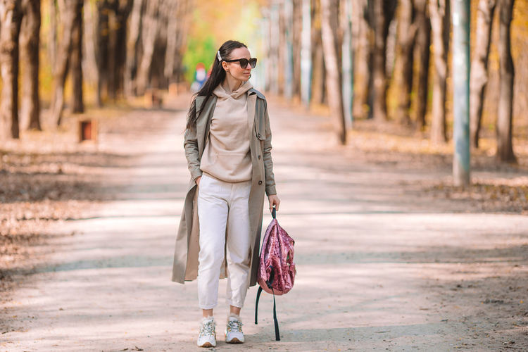 Woman with umbrella walking on footpath in forest