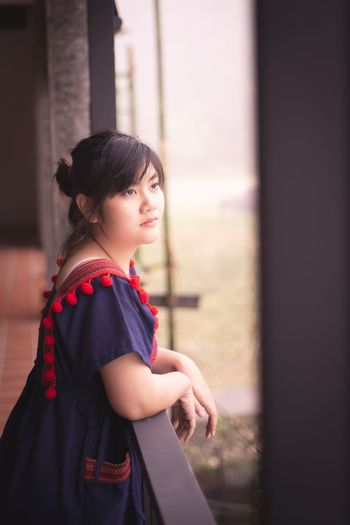 Side view of thoughtful woman looking away while standing by railing