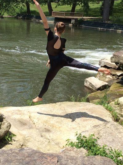Full length rear view of ballerina dancing by lake in park