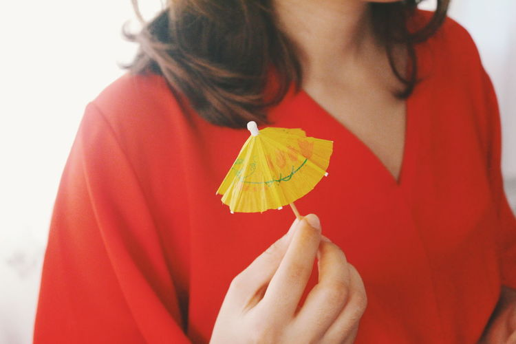 Midsection of woman holding yellow drink umbrella