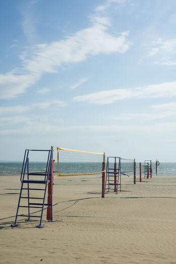 Sports net on beach against sky
