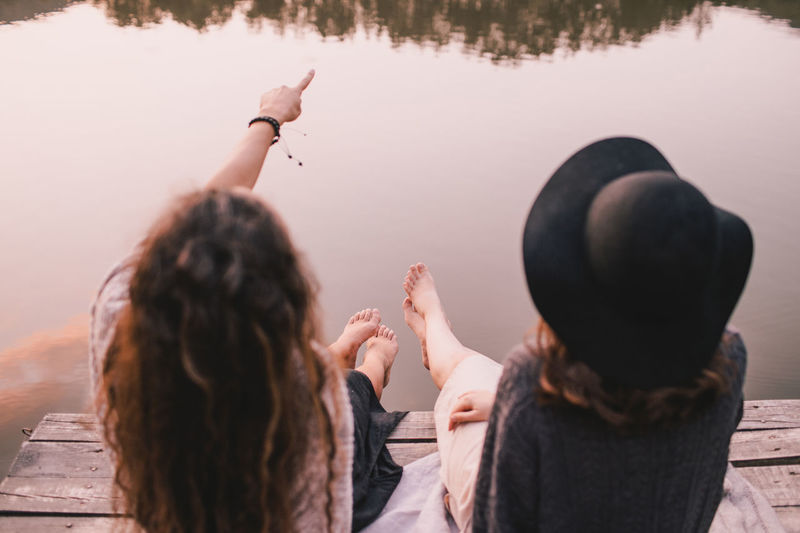 Rear view of female friends sitting on pier