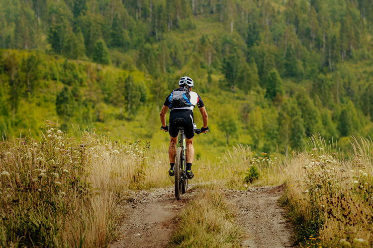 Back male cyclist with backpack on mountain bike riding trail in grass field