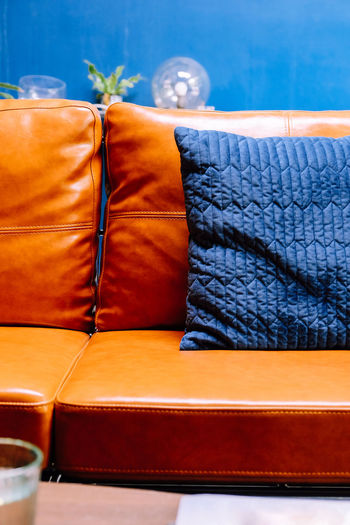 Close up detail of blue pillow on leather sofa Decor Leather Living Orange Pillow Absence Blue Brown Close-up Comfortable Cushion Decoration Decorations Decorative Elégance Furniture Furniture Details Home Interior Indoors  Interior Design Leather Leather Sofa Living Room Luxury Modern No People Orange Color Pattern Relaxation Seat Sofa Stuffed Wealth Wood - Material