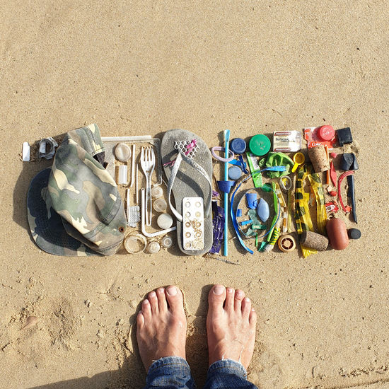 Low section of person standing barefoot next to trash and plastics collected from the beach