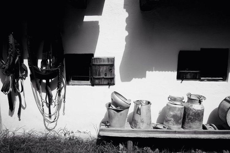 Milk canisters on shelf against farm
