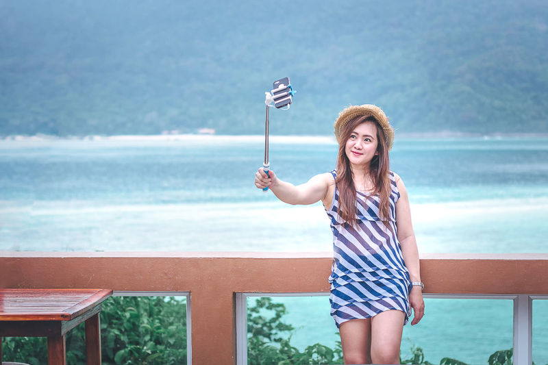 Woman taking selfie through mobile phone against sea