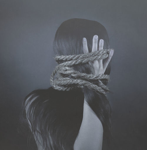 Woman with tied hair against gray background