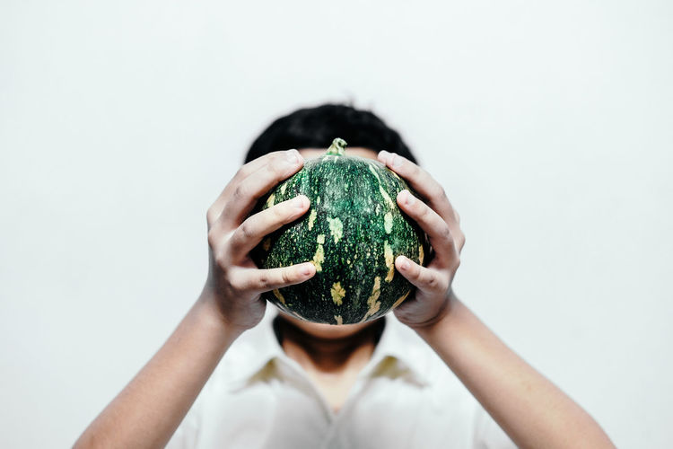 Boy Covering Face With Watermelon Against White Background